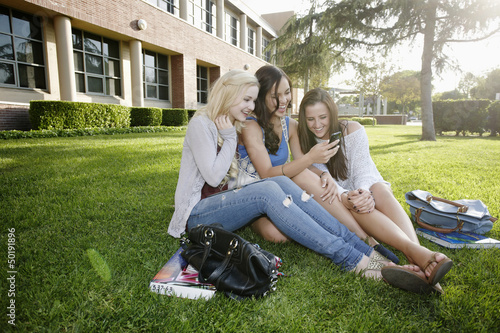 School friends sitting in grass looking at cell phone
