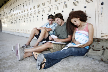 School friends doing homework together near lockers