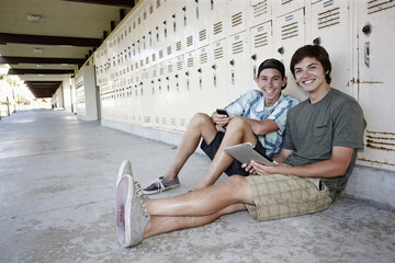 School friends leaning on lockers using digital tablet