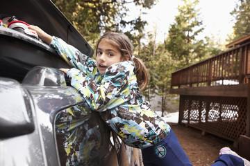 Mixed race girl packing car