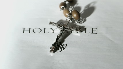 Rosary beads falling onto first page of holy bible