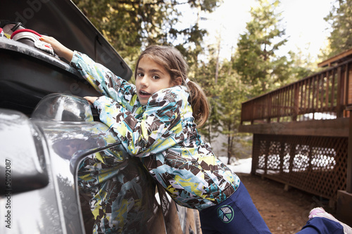 Mixed race girl packing car