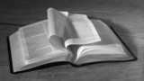 Bible pages turning in the wind in black and white