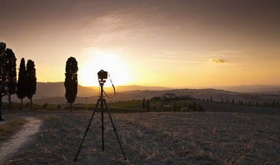 Camera in field on tripod at sunset
