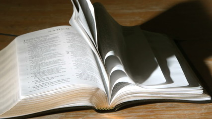 Bible pages turning in the wind