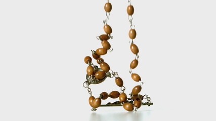 Rosary beads falling onto white surface
