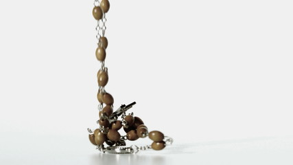 Rosary beads falling onto a white surface