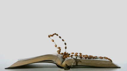 Rosary beads falling onto open bible on white background