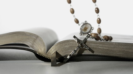 Rosary beads falling onto open bible on close up