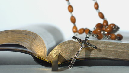 Rosary beads falling on open bible on white background close up