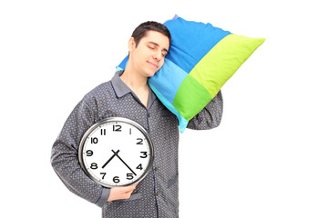 A young lazy guy holding a clock and sleeping on a pillow