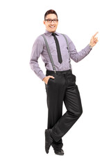 Full length portrait of a stylish smiling male pointing