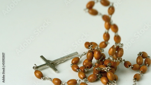 Rosary beads falling on white surface