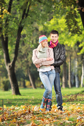 A loving couple hugging in park in autumn