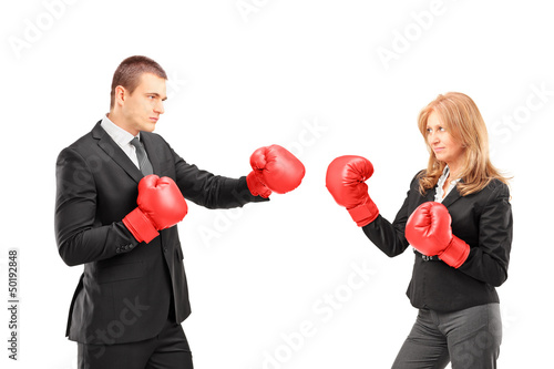 Businesswoman with boxing gloves having a fight with a businessm