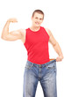 Weight loss man showing his muscles and holding an old pair of j