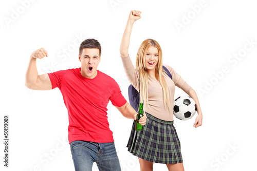 Young male and female football supporters cheering