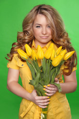 Beautiful Girl With Tulip Flowers over green background. Beauty
