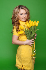 Happy smiling girl with spring-flowering yellow tulips isolated