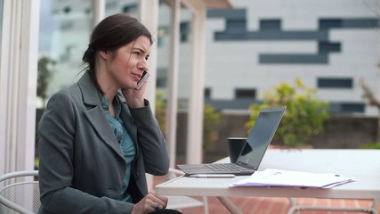 Businesswoman working with cellphone and laptop on terrace