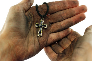 Dirty hands holding cross