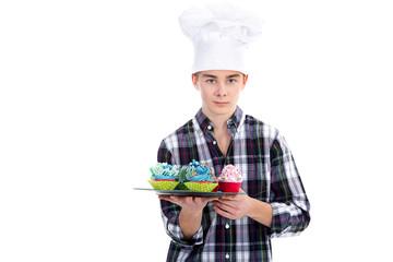 Junger Bäcker mit Cupcakes lächelt freundlich und serviert