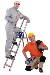 Painter on a ladder and crouching electrician