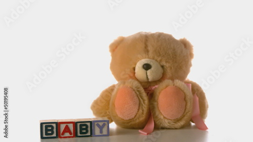 Teddy bear falling besides baby blocks