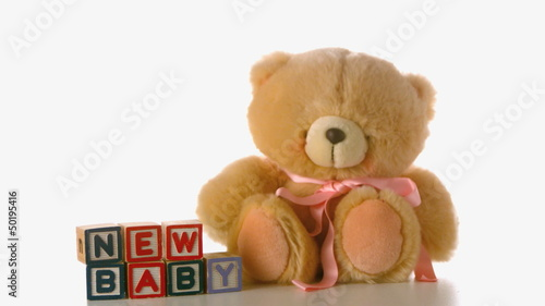 Cute teddy bear falling besides baby blocks