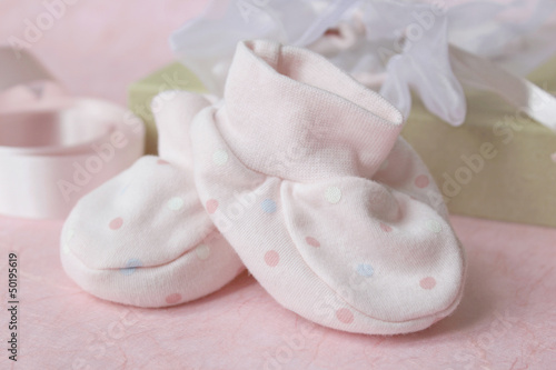 Pink spotted baby bootees with gift bag and pink ribbon