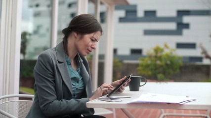 Businesswoman working on tablet computer on terrace