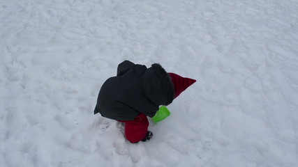 girl tries to dig the frozen snow with a small green trowel