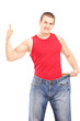 Weight loss man giving thumb up and holding an old pair of jeans