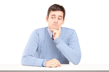 Worried young man sitting at a desk