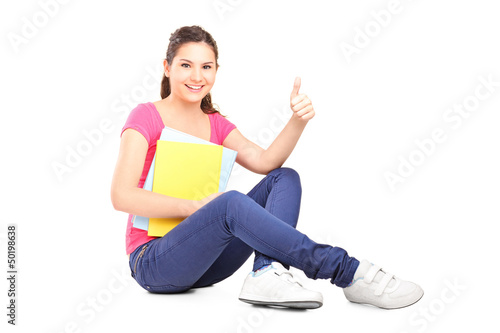 Young female student sitting on floor and giving thumb up