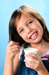Happy young girl eating probiotic yoghurt