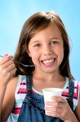 Happy young girl eating probiotic yoghurt
