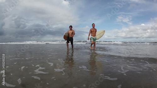 Two happy young surfers holding their surf boards and walking