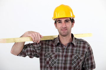 A carpenter carrying a plank.