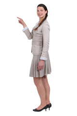 smiling young woman pointing at someone isolated on white