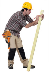 Man marking a measurement on a wooden plank