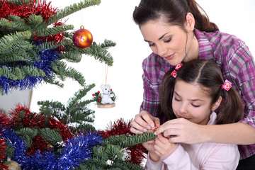 Mom and daughter decorating the Christmas tree