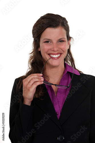 Woman nibbling at the frame of her glasses