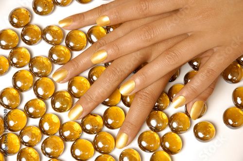 Woman hands manicure with gold nail polish