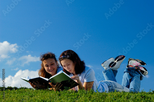 Two girls reading books outside
