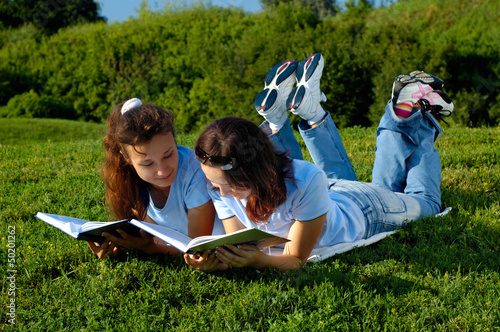 Two girls reading books outside in a park