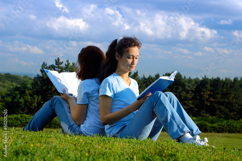 Two girls students studying reading outdoors