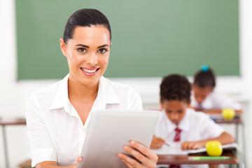 school teacher using tablet computer in classroom