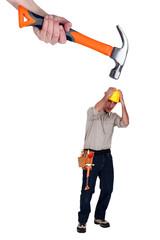 Scared builder shielding himself from giant hammer