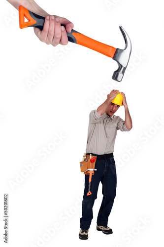 Scared builder shielding himself from giant hammer